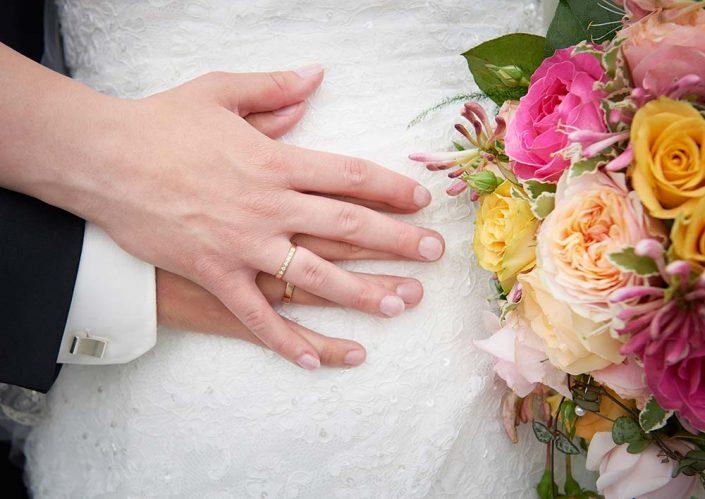 Nærbillede af hænder og brudebuket