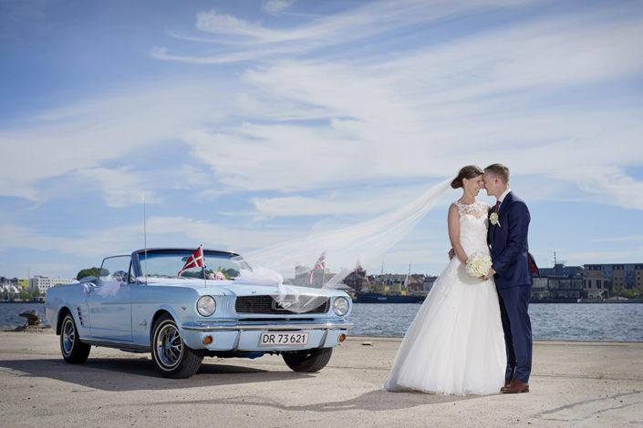 Bryllupsfotografi brudepar med bil på havnefront